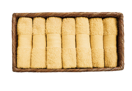 Small yellow towels in basket isolated over white background. Top view
