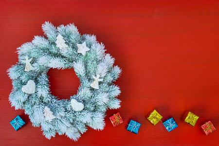 White Christmas wreath with Christmas ornaments on red background. Christmas greeting card. Copy space, top view Фото со стока