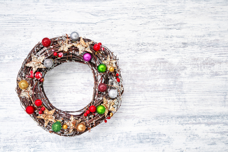 Christmas wreath with decoration on white wooden background. Copy space, top view. Christmas background