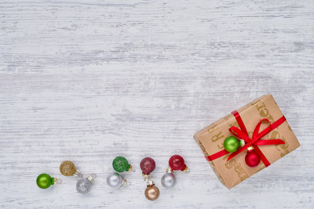 Christmas background. Christmas gift box and Christmas ornaments on white wooden background. Top view, copy space