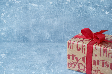 Gift box wrapped in christmas paper on blue background. Copy space, snow texture. Christmas greeting card. Фото со стока