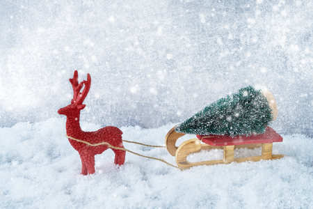 Christmas composition with deer and fir tree on sledge in snow. Copy space