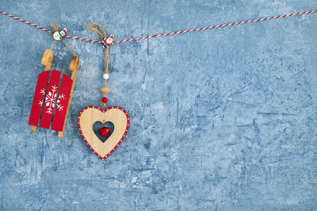 Christmas background. Red Christmas decoration hanging on rope on blue background. Copy space.