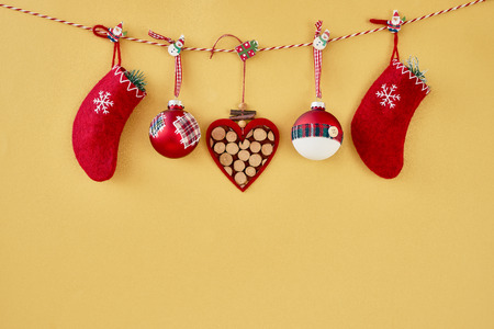 Christmas background. Christmas ornaments, red christmas socks and heart hanging on rope on golden background. Copy space.