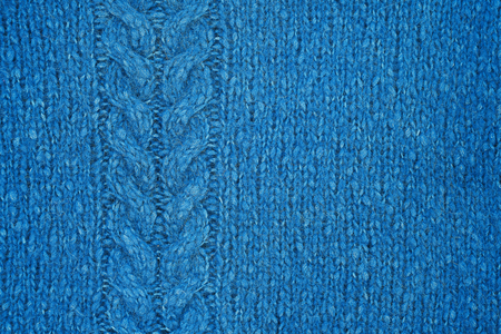 Blue knitted texture with a relief pattern. Handmade Knitwear. Background, abstract.
