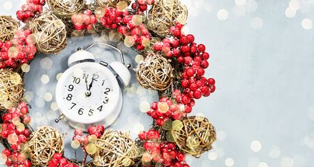 Christmas background. Christmas wreath with decoration and alarm clock on blue background. Copy space, top view