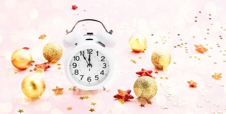 Christmas background. Christmas decoration and white vintage alarm clock on pink background. Copy space for text