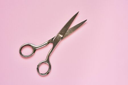 Single old soviet scissors on pink background. Opened. Top view, copy space fortext