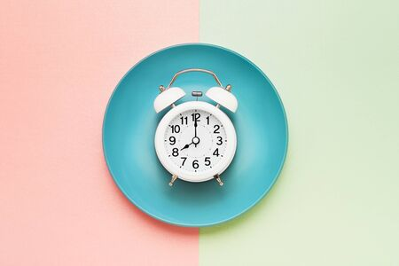 Intermittent fasting concept. White alarm clock on empty blue plate on pink-green. Eight hour feeding window concept. Flat lay, copy space.