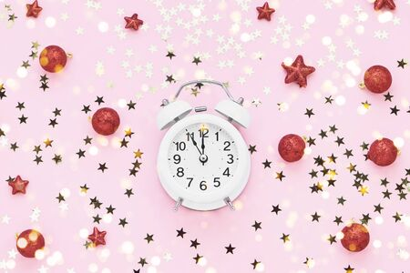 Christmas decoration and white vintage alarm clock on pink background. Top view, copy space.