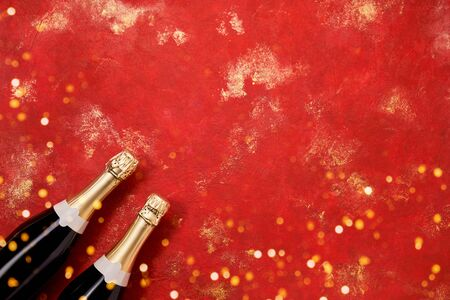Two Champagne bottles on bright red background. Holiday background. Christmas, New Year or birthday concept. Copy space, top view Reklamní fotografie