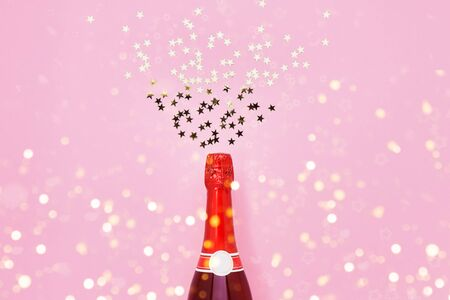 Red Champagne bottle with confetti stars on pink background. Christmas, birthday, bachelorette or wedding concept. Top view, copy space