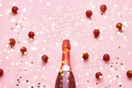 Red Champagne bottle with red Christmas decoration on pink background. Top view, copy space Reklamní fotografie