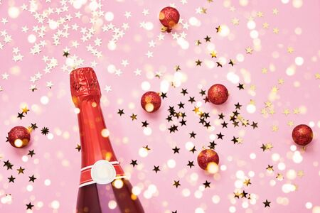 Red Champagne bottle with red Christmas decoration on pink background. Holiday background. Top view, copy space