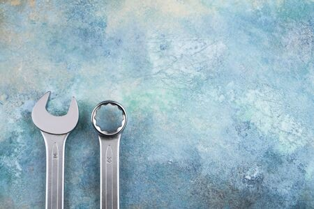 Two Wrench spanner tools on grunge colorful background. Top view, copy space for text