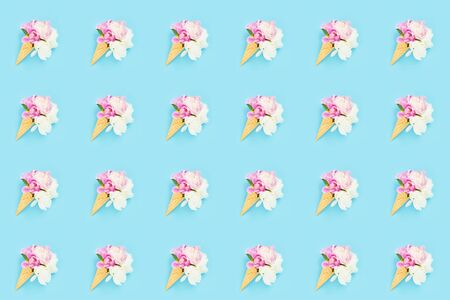 Peonies flowers bouquet in waffle ice cream cone on light blue background. Seamless pattern. Summer concept. Flat lay Foto de archivo