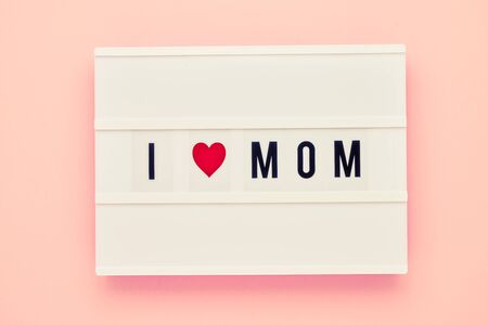 I LOVE MOM written in light box on pink background. Mothers Day celebration concept. Top view, copy space for text 写真素材