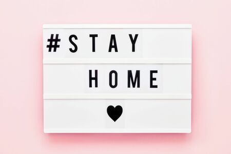 STAY HOME written in light box on pink background. Healthcare and medical concept. Top view, copy space. Quarantine concept.