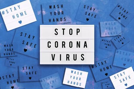 STOP CORONA VIRUS, STAY HOME, STAY SAFE and WAHS YOUR HANDS written in light box on blue background. Healthcare and medical concept. Top view. Quarantine concept.