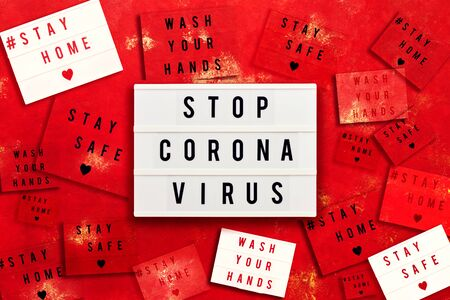 STOP CORONA VIRUS, STAY HOME, STAY SAFE and WAHS YOUR HANDS written in light box on red background. Healthcare and medical concept. Top view. Quarantine concept.