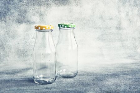 Two empty glass bottles with colorful lid on grey background. Copy space