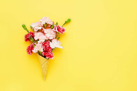 Waffle ice cream cone with red and pink carnation flowers on bright yellow background. Summer concept. Copy space for text, top view Stockfoto
