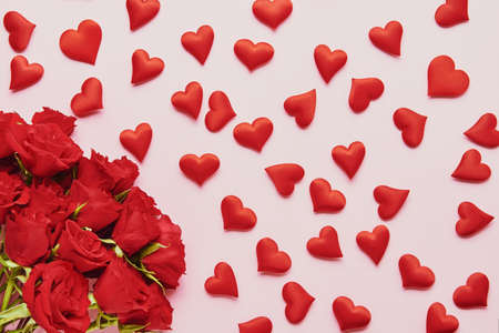 Valentines Day concept. Red hearts and red roses flower bouquet on a pink background. Flat lay Standard-Bild