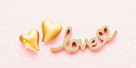 Two golden hearts and word LOVE on pink background. Valentines Day concept.