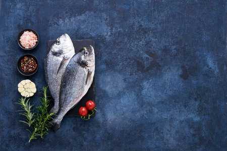 Raw dorado fish with spices on a slate cutting board on a blue background. Mediterranean seafood concept. Top view, copy space for text 免版税图像