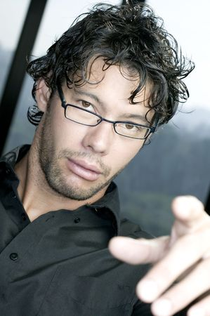 Young man with glasses pointing at the camera photo