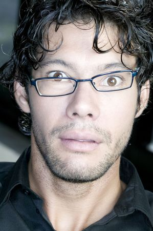 Young man with glasses making funny face photo