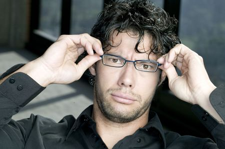 laughable: Young man holding his glasses