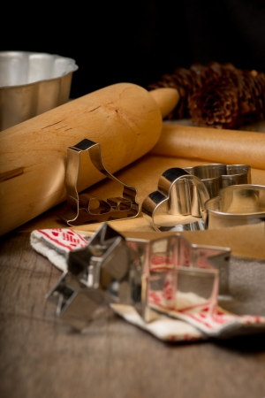 Gingerbread cutters and Christmas linen next to rolling pin on wooden table with baking mold,  spruce cones and brown paper on background. Vertical. Christmas card. photo
