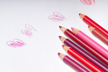 Red and pink coloring pencils on top of white  paper with naive hearts drawn on it. Horizontal  close-up. Different colors of red. photo
