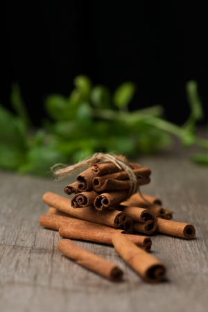Pile of cinnamon sticks on top of wooden table before fresh basilica with black bacground. Vertical photo. Selective focus on cinnamon sticks. Recipe book photography. photo