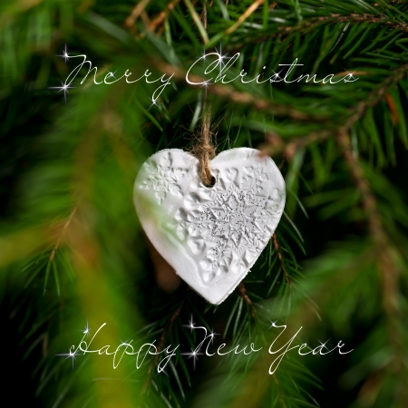 Merry Christmas and Happy New Year text. Square photo. Single Christmas tree ornament hanging in the tree. Selective focus on handmade ornament in center of photo. photo