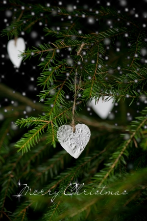 Merry Christmas text. Heart shaped christmas decorations hanging on christmas tree. Selective focus on handmade ornament. Snowing in front of christmas tree. Vertical photo. photo