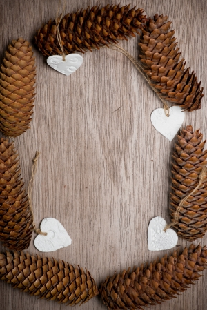 Heart shaped Christmas decorations and spuce cones frame on wooden table. Merry Christmas. vertical photo. handmade ornaments. Empty wooden background in center of photo for your own text or message. greeting card. photo