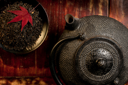 red maple leaf: Japanese iron teapot and heap of tea leaves from top  Red maple leaf on top of tea leaves