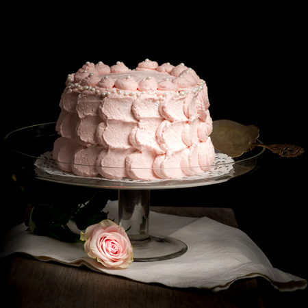 Scalloped pale pink cake on glass stand next to rose on wooden table. Still live photo, no people. Stock Photo - 26183894