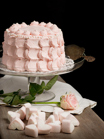 Scalloped pale pink cake on glass stand next to rose and marsmallows on wooden table. Still live photo, no people. Stock Photo - 26183876