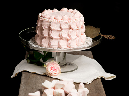 Scalloped pale pink cake on glass stand next to rose and marsmallows on wooden table. Still live photo, no people. Stock Photo - 26183933