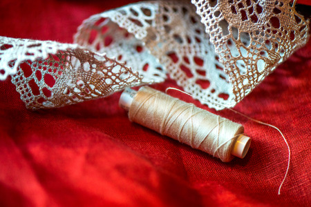 A macro shot of beige thread spool and a white, crochet natural linen lace trim on a dark red linen fabric, being used while sewing tablecloths, napkins and towels by using a sewing machine Stock Photo
