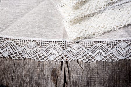 white trim: Macro shot of linen tablecloths and napkins with snow white crochet lace trim on a wooden table