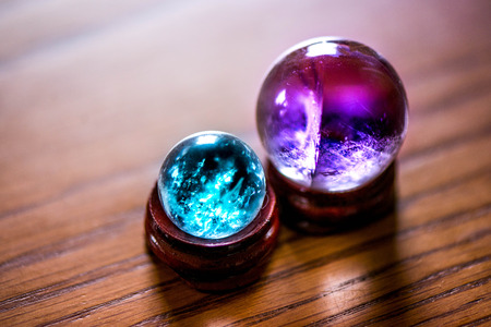 Fortune telling. A macro shot of purple, blue and turquoise glass balls on a wooden pad, with sun reflections, bubbles and a rainbow in it,standing on a pine dining table in the middle of a kitchen.