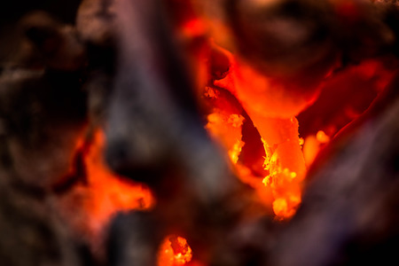 Ignite the fire. Warming up the cold winter nights. A macro shot of firewood, white dust and hot, glowing coal. Burning branches and wood. Flames in the fireplace, cozy home, warmth, love, romantic