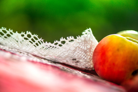 Golden autumn. Macro shot of crochet white linen lace trim, natural linen tablecloth with rose print, red, yellow apples on table on green background. Time for dinner. Perfect time for picnic outside