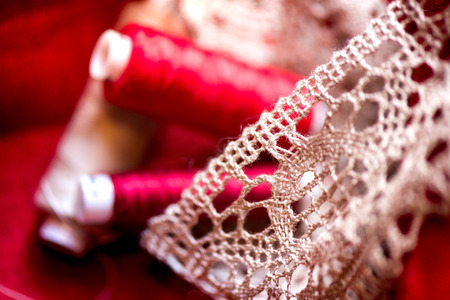 A macro shot of a red and white thread spools and a white, crochet natural linen lace trim on a dark red linen fabric, being used while sewing tablecloth by using a sewing machine Stock Photo