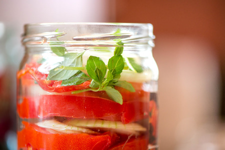 Canning fresh tomatoes with onions for winter in jelly marinade. A shot of basil leaves on top of a red ripe tomato slices and onions being put in jar Stock Photo