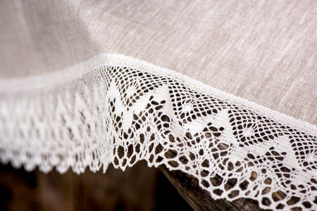 white trim: Macro shot of a linen tablecloth with white lace trim on a wooden table